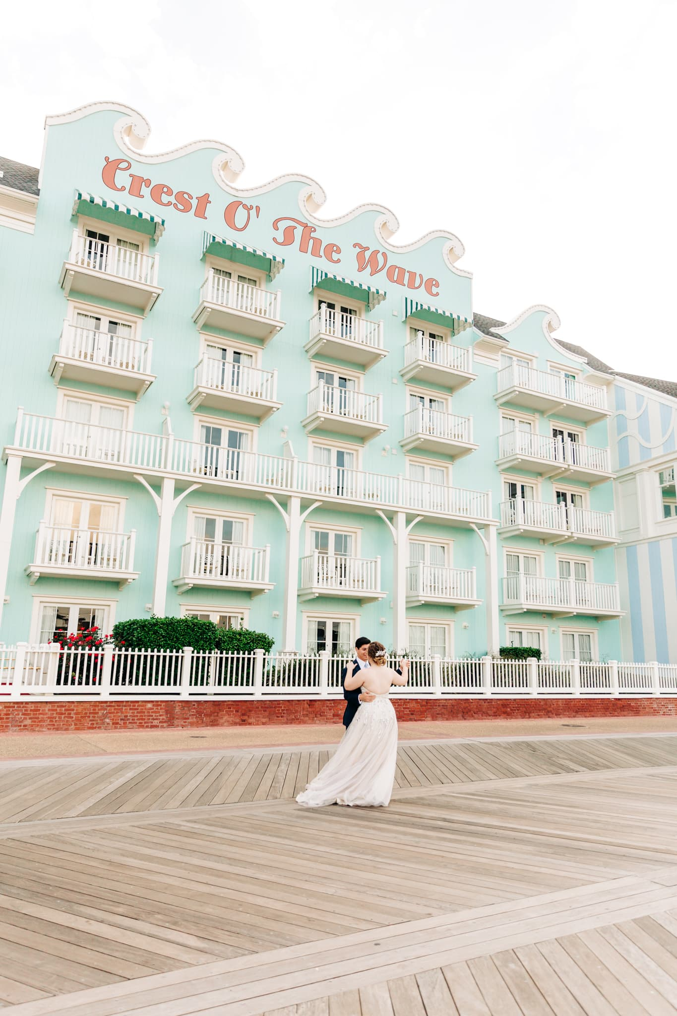 couple slow dancing on the Disney boardwalk in front of the crest of the wave blue hotel on the lake