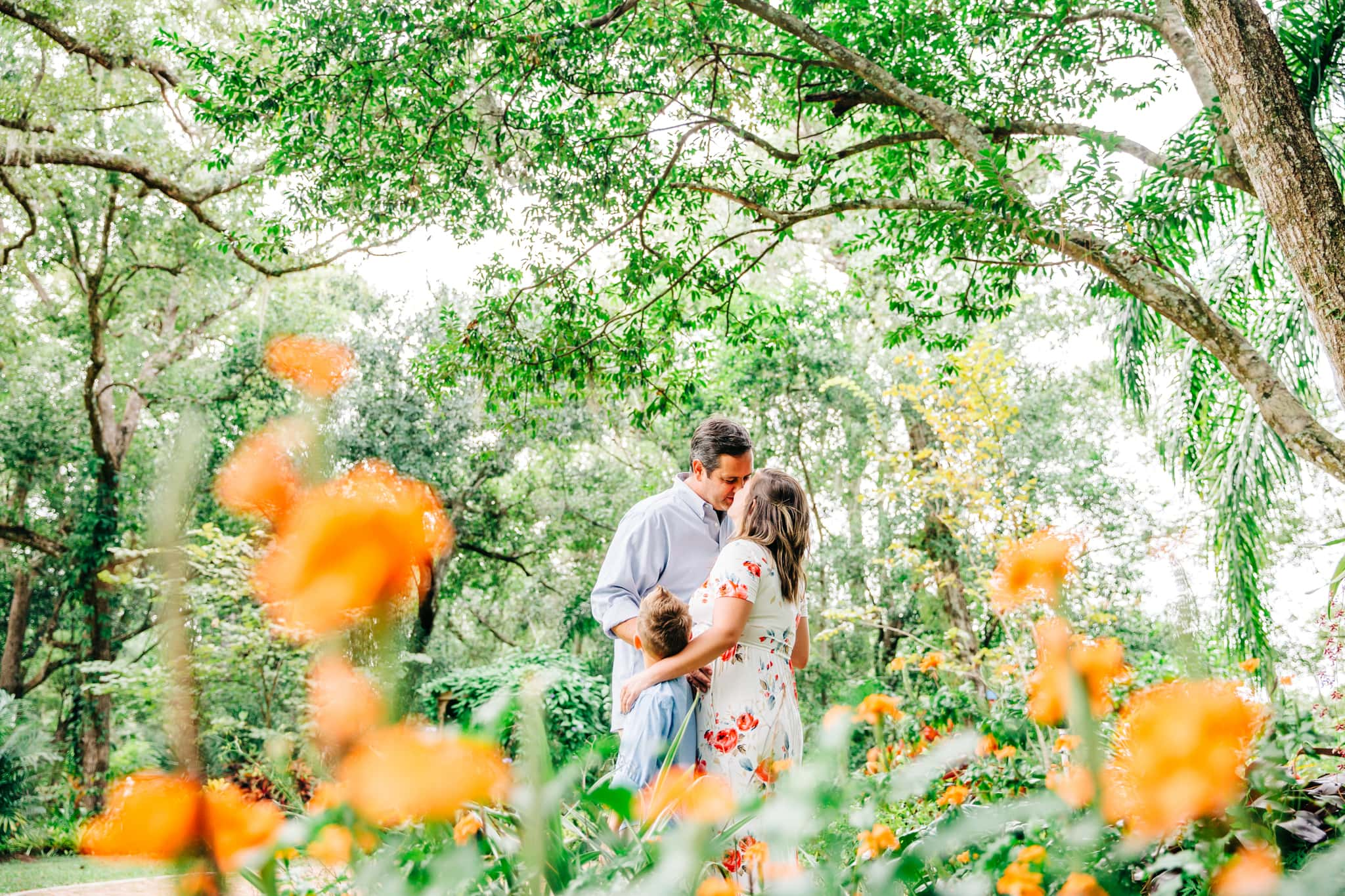 pregnant woman kissing husband in mead gardens while being hugged by their small son