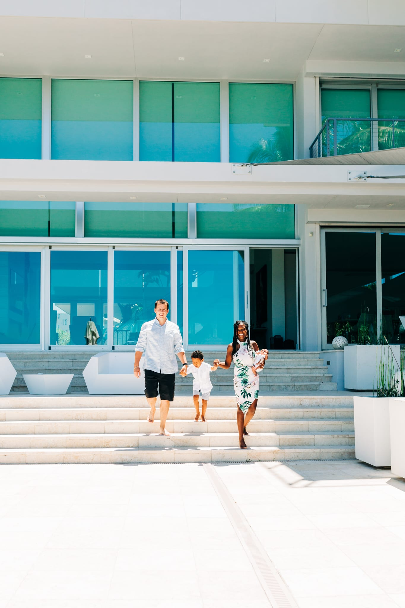 family walking down steps of grand house with glass windows holding a newborn baby and toddler