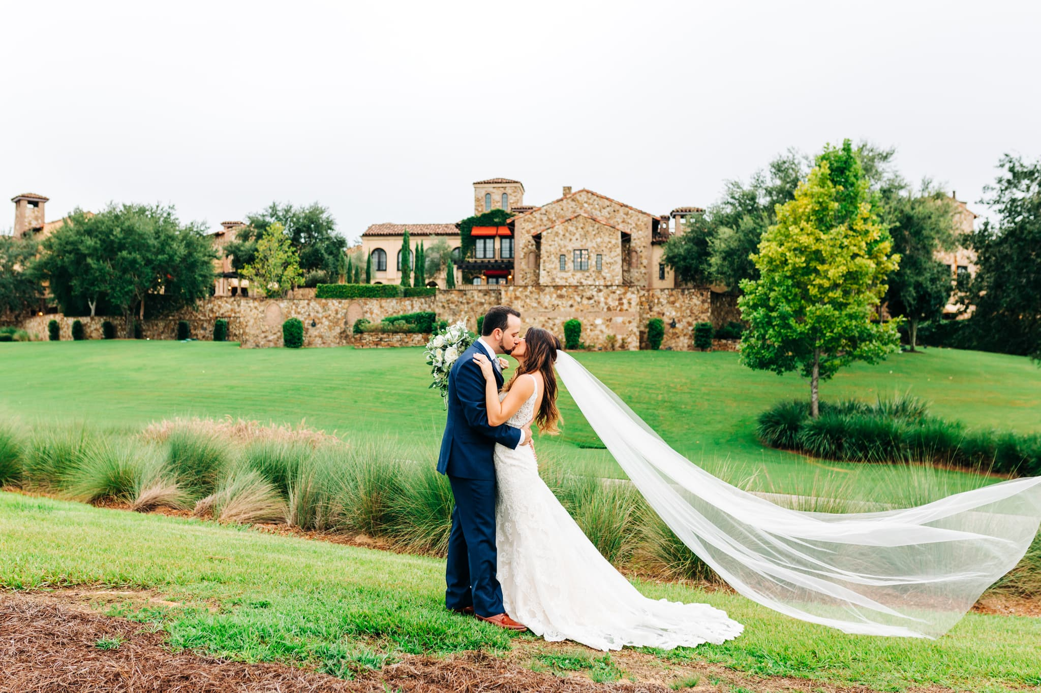 bride with cathedral veil flying in the wind kissing groom on golf course in front of Bella Collina with wedding venue in the background