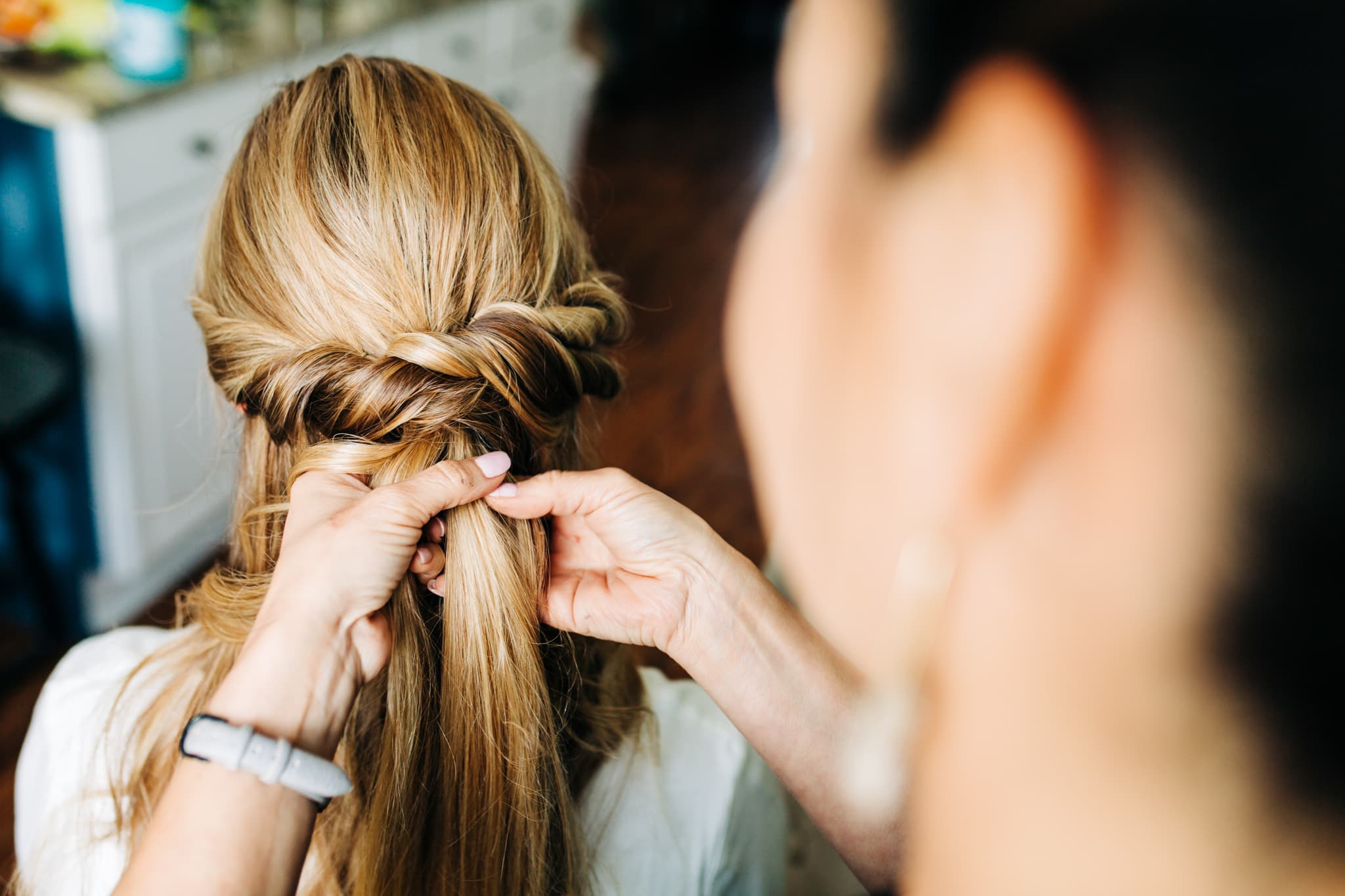bride getting hair braided by hair and makeup artist before wedding