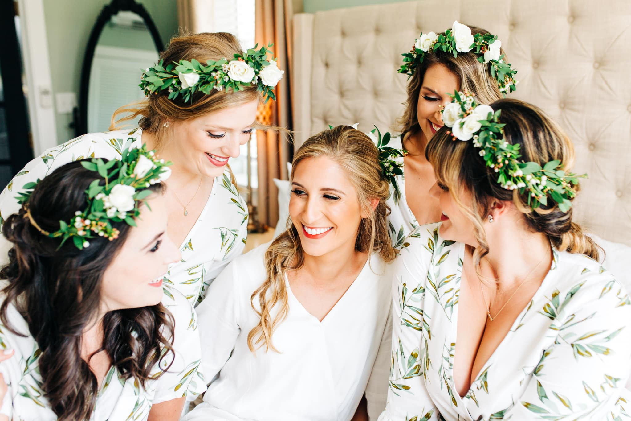 bride at Bella bay in laughing with bridesmaids in white and green flower crowns and bridesmaid robes