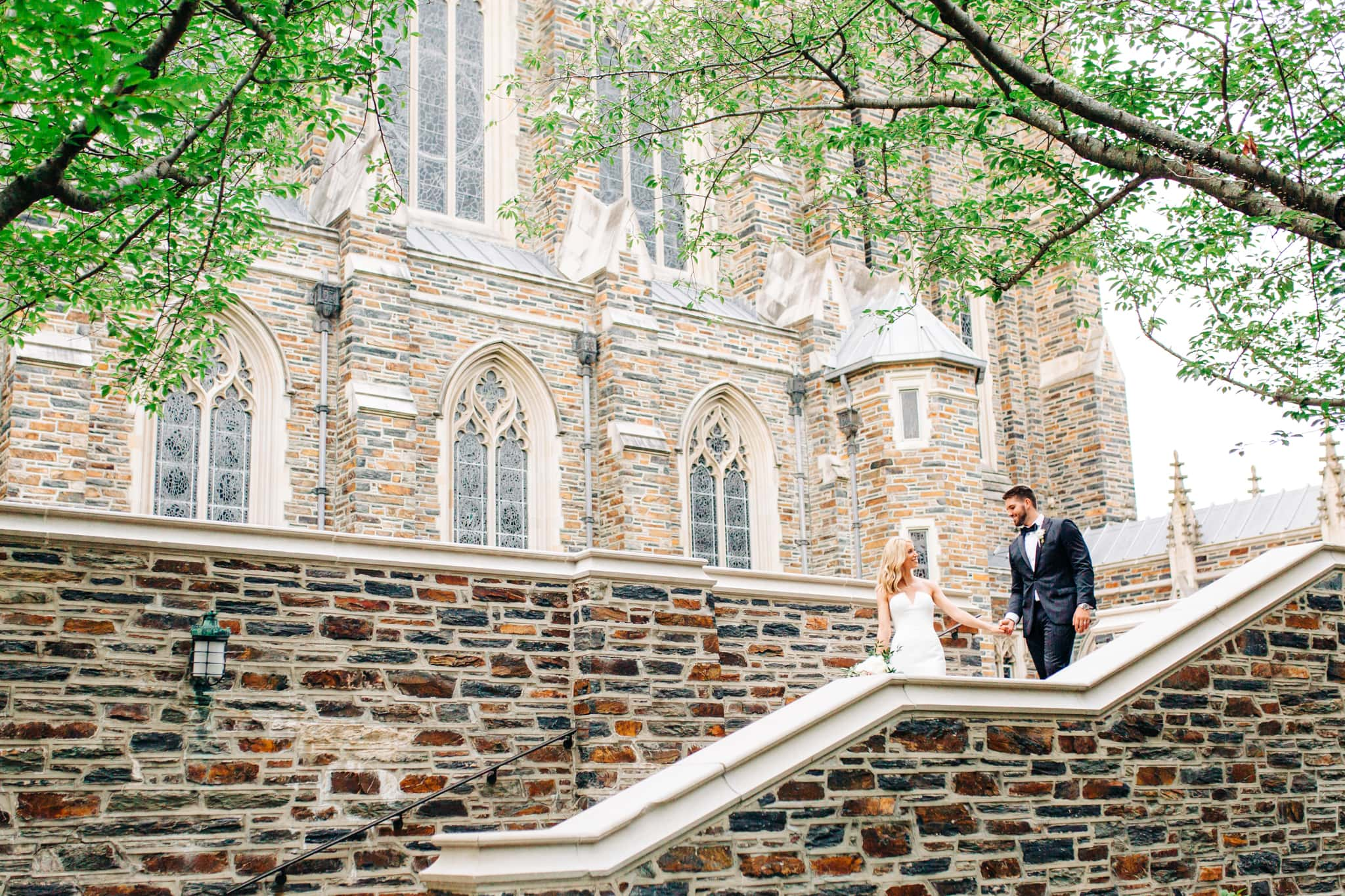 bride leading groom down the stone stairs at duke university after just getting married in the chapel