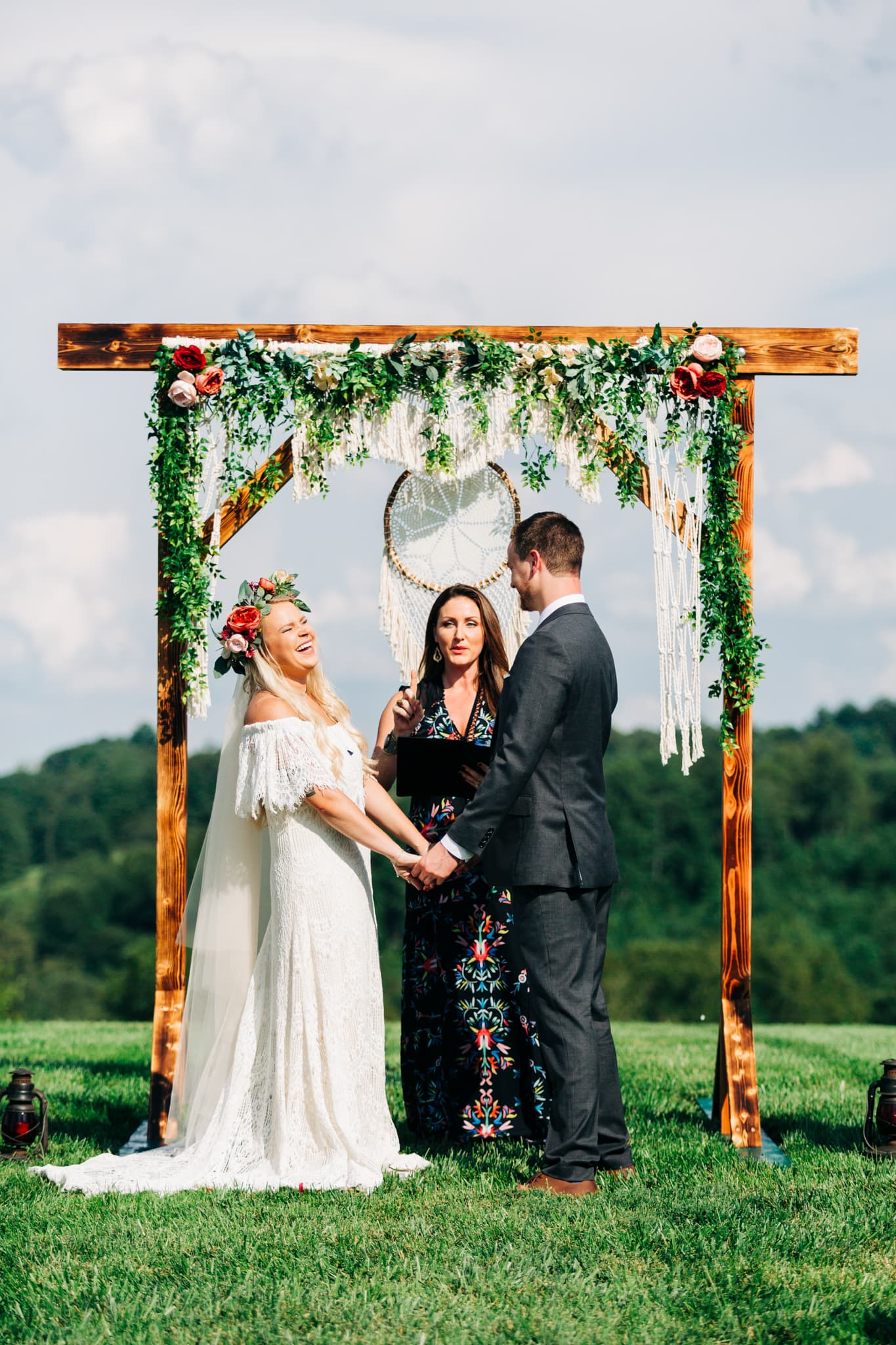 bride laughing during vows underneath wooden arch boho flowers and crochet backdrop