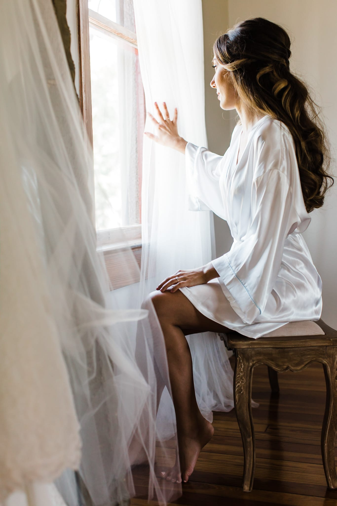 bride in white robe looking out the window with a breeze coming through
