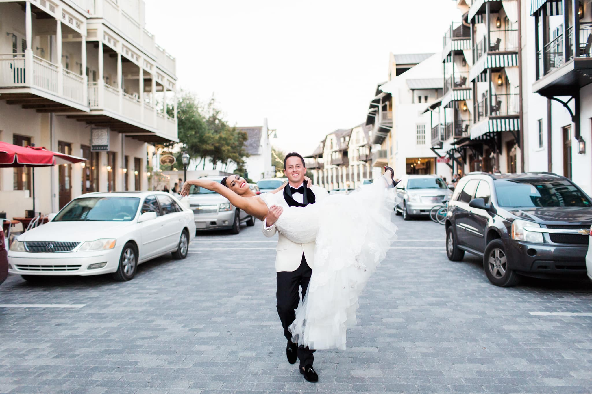 groom carrying bride through the street in rosemary beach florida in front of the pearl wedding venue