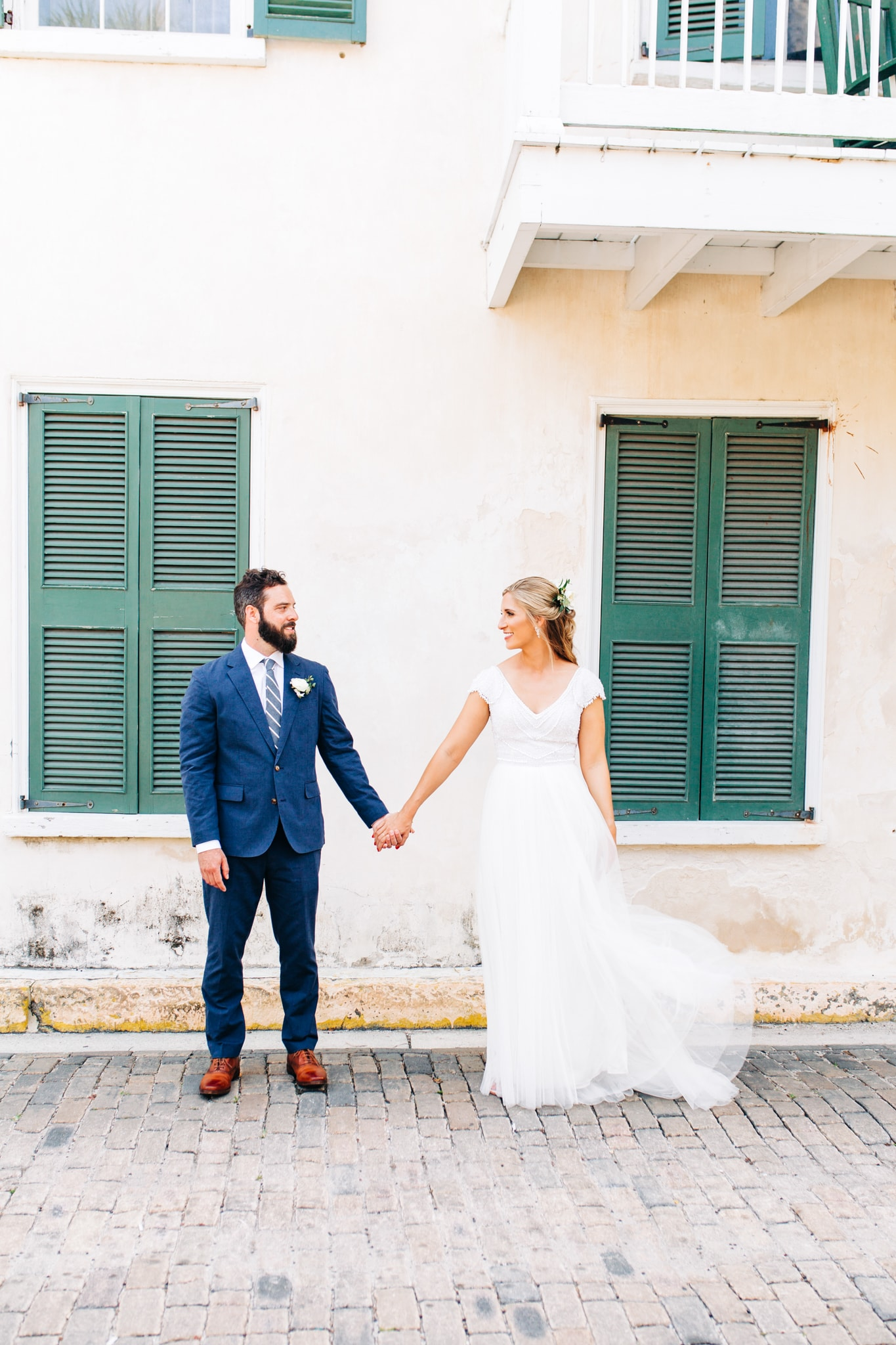 bride and groom holding hands between green windows with wind making wedding gown flutter in the wind