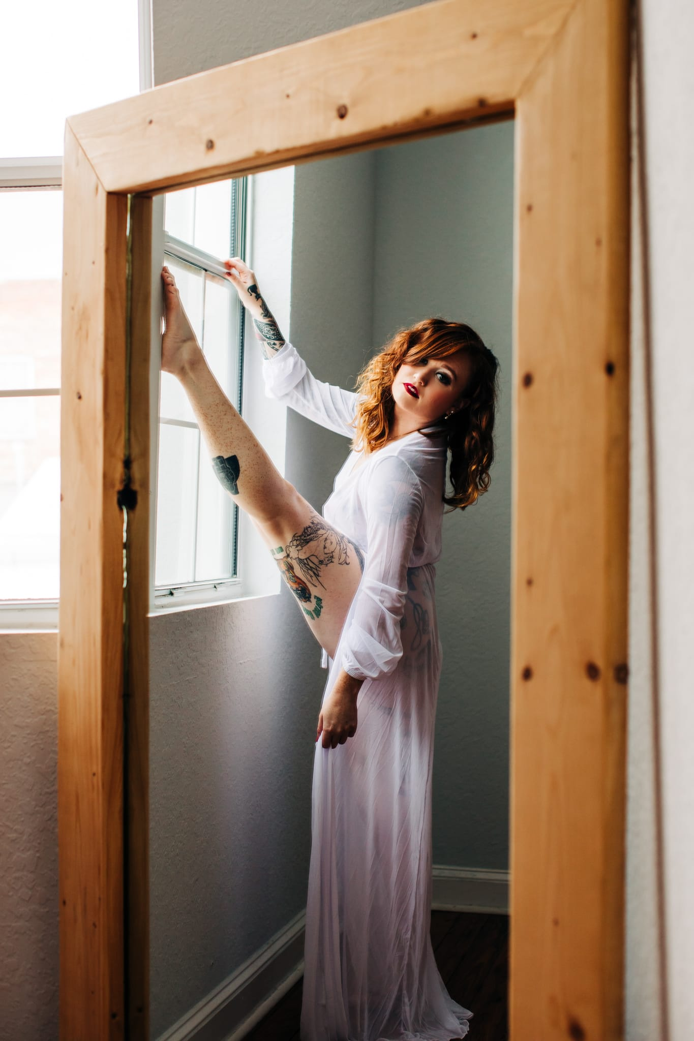girl stretching in mirror reflection with long white robe on