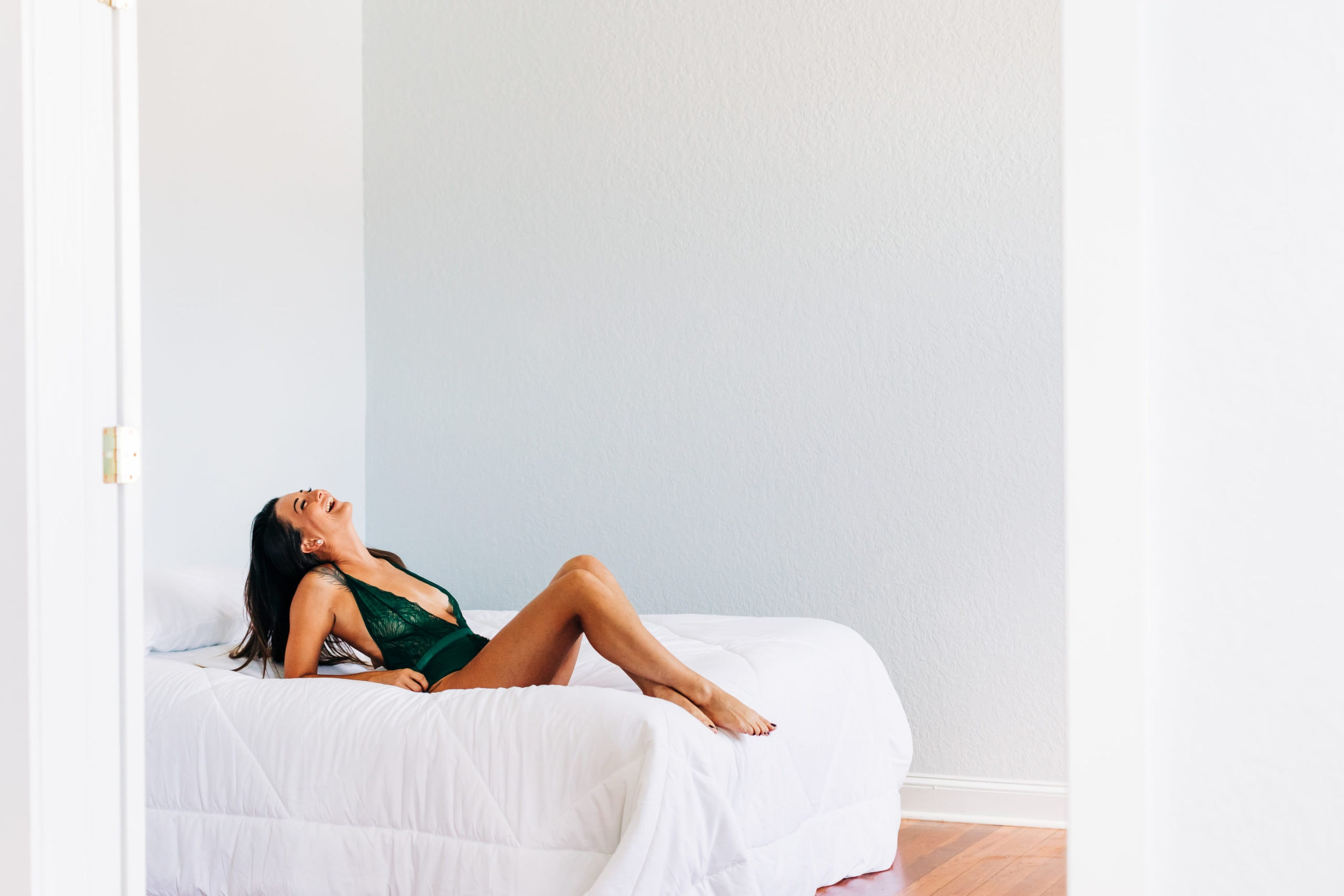 woman in green lingerie laughing in bed