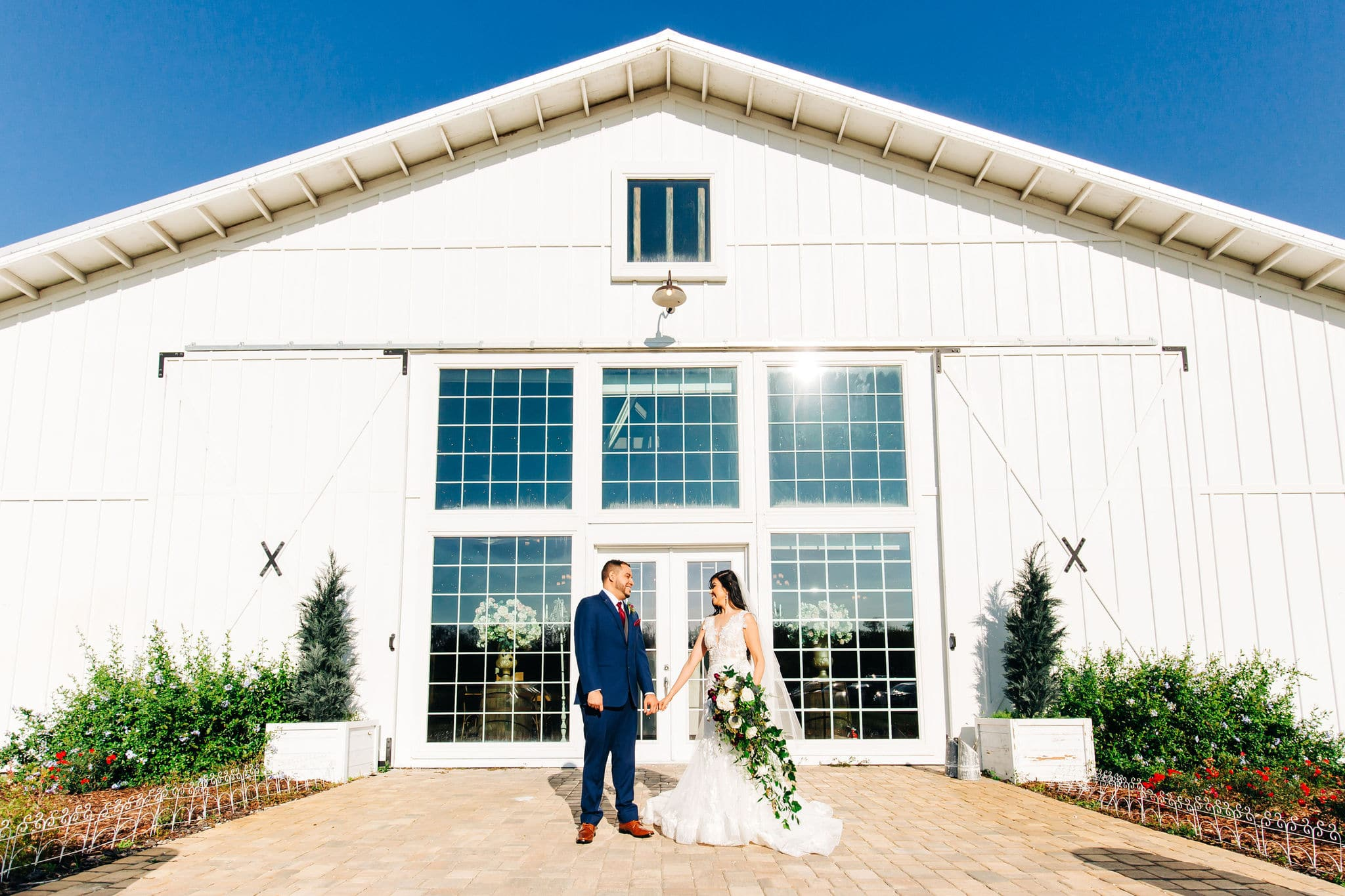 large white barn with large glass windows with bride and groom with navy suit with large bouquet at Game of Thrones Wedding