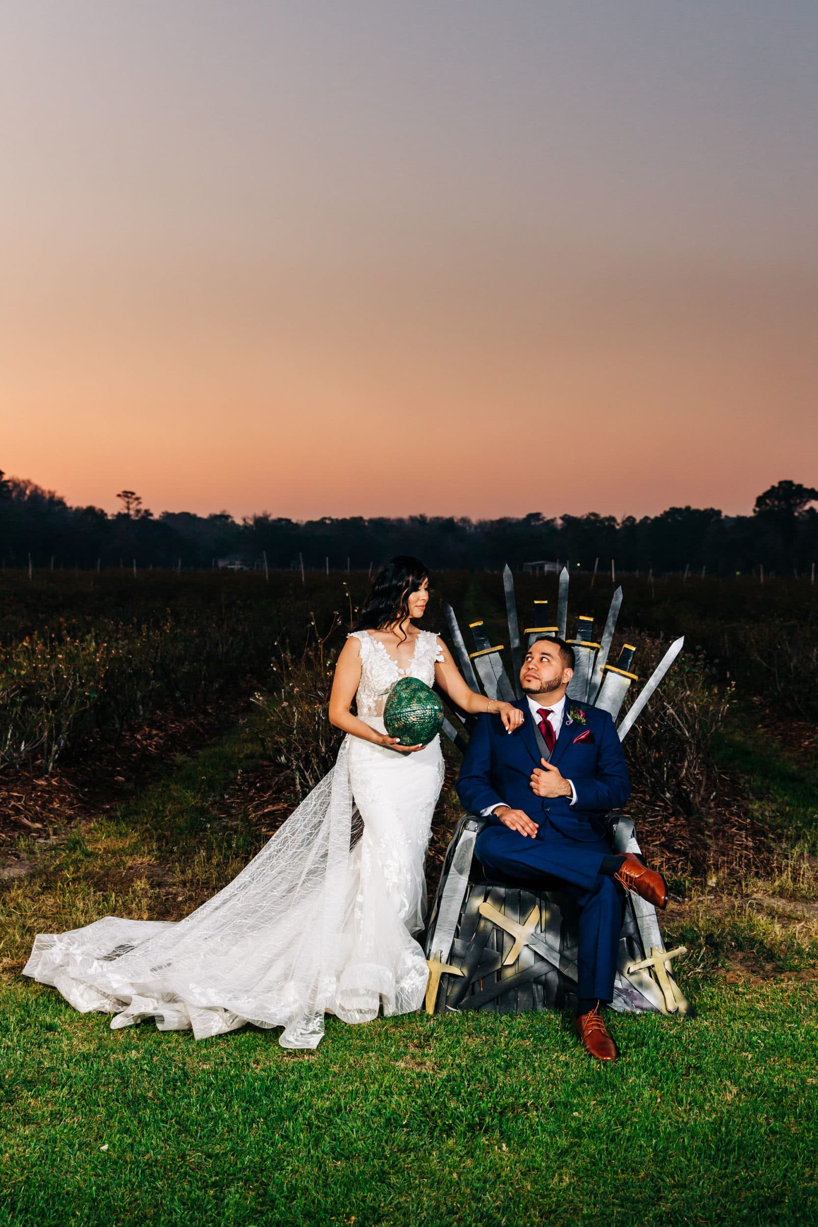 bride in white dress with green dragon egg with groom in navy suit with red tie with iron throne at Game of Thrones Wedding