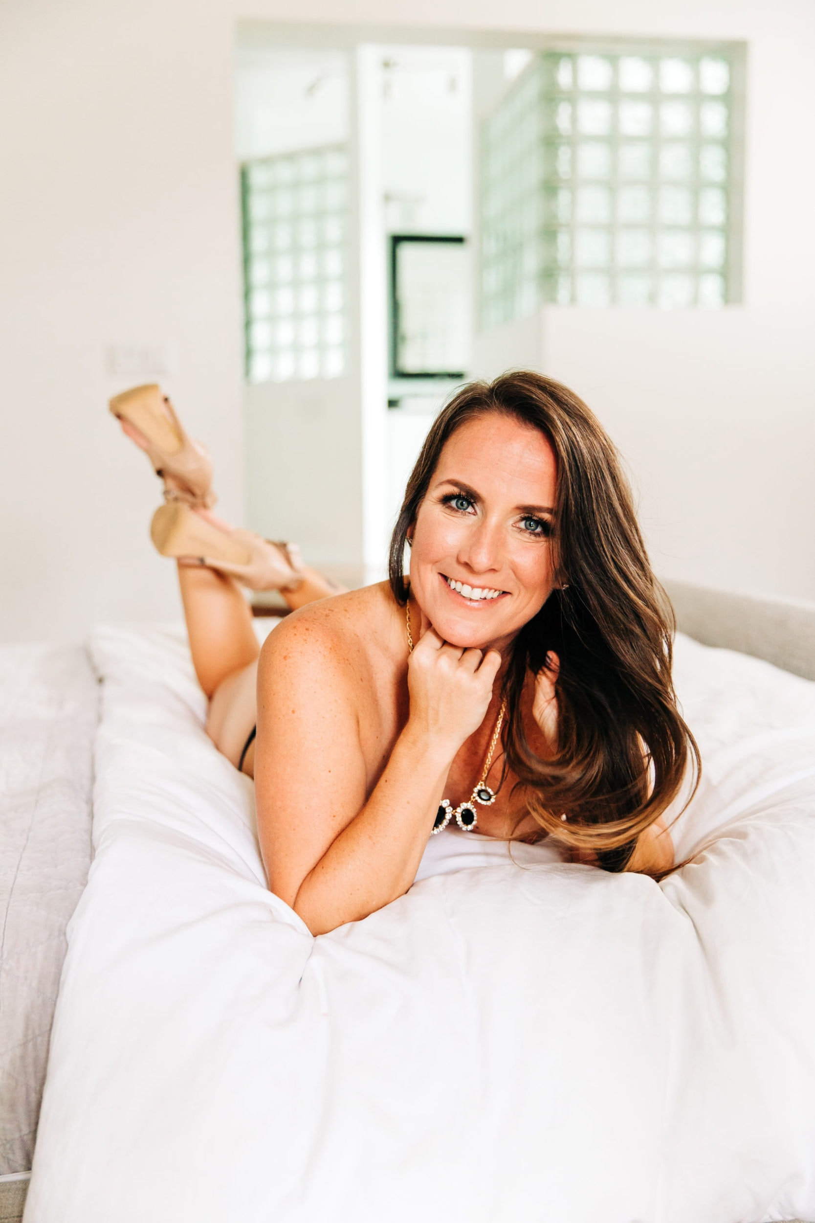 Girl laying on white bed for boudoir session