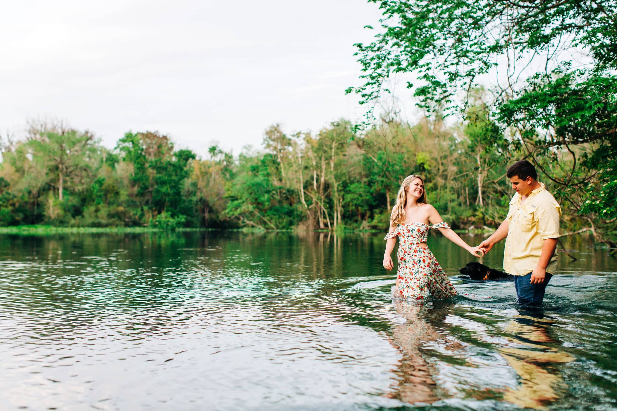 bride to be with groom to be holding hands walking through water at Wekiwa Springs Adventure Engagement Session