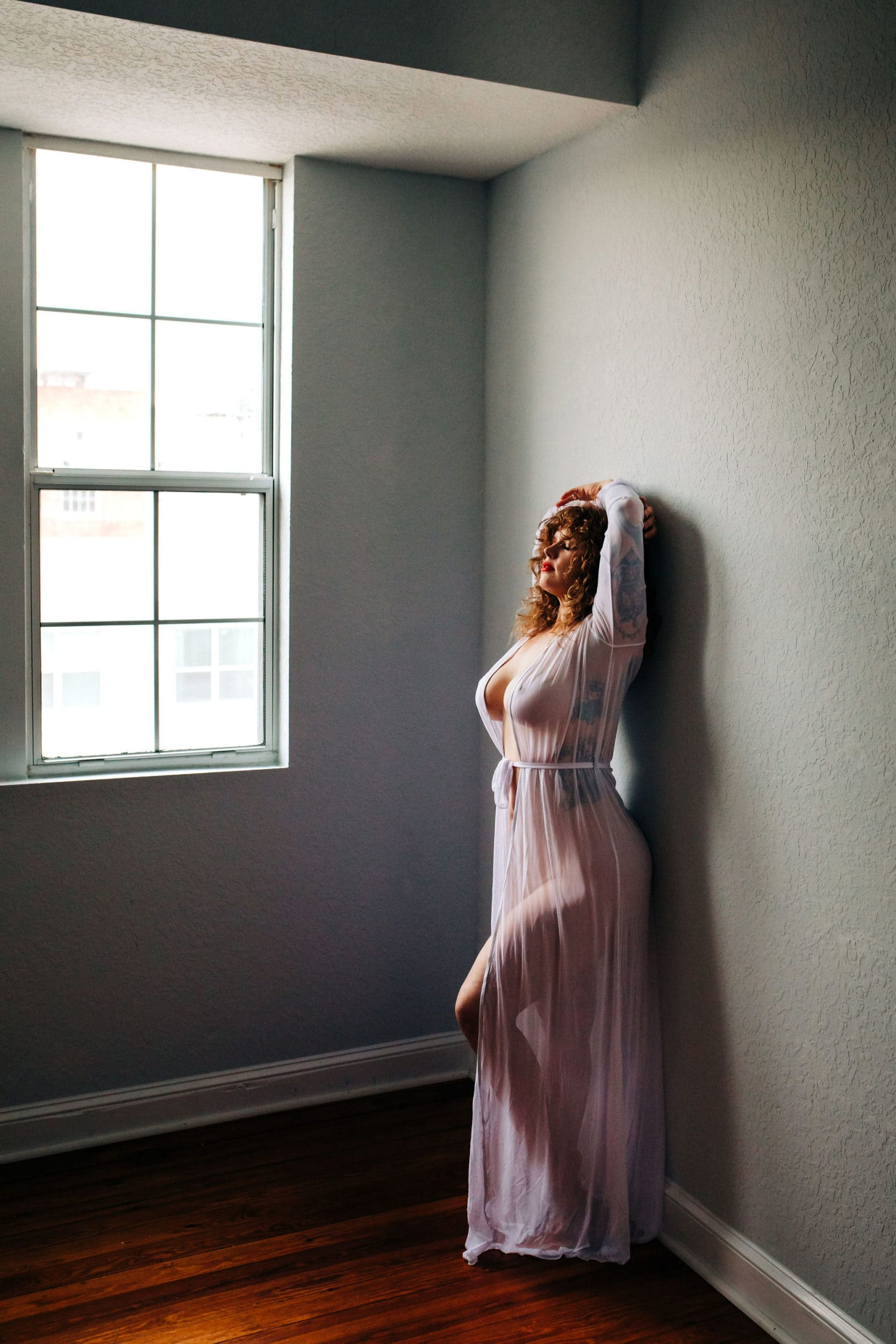 Redheaded girl standing in window light at Sara Ozim photography studio
