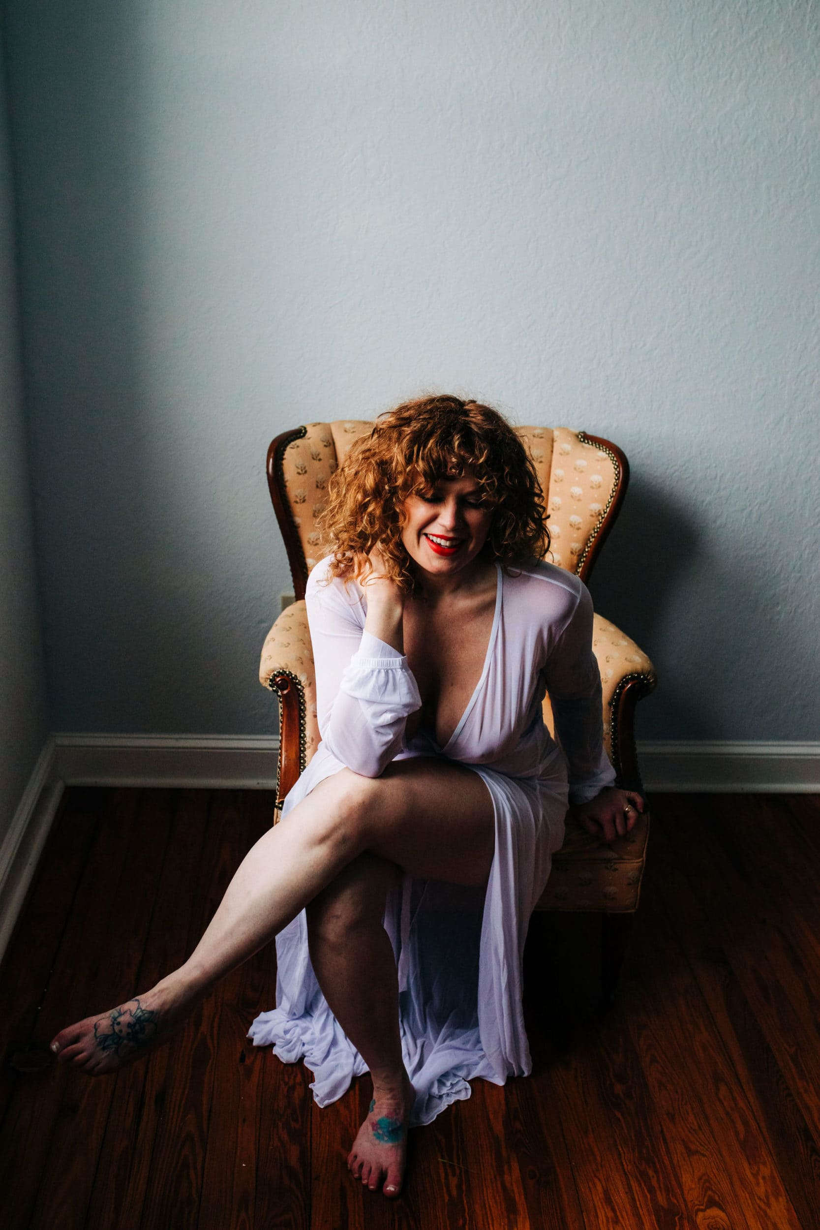 redheaded girl in white robe sitting in yellow chair